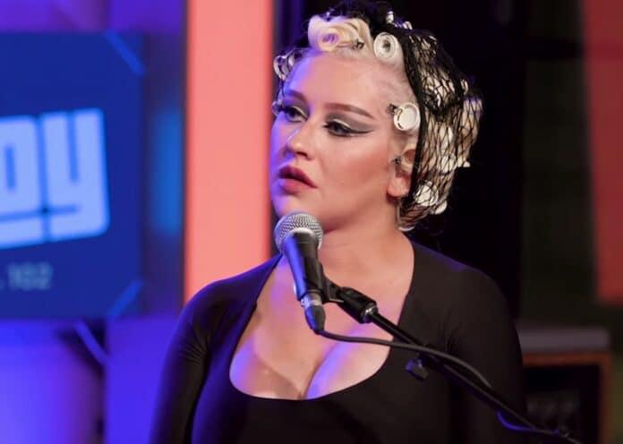 Christina Aguilera, una mamma premurosa La trentottenne ha mostrato il suo lato giocoso in una felpa blu di Gucci con una foto di Topolino sul davanti.